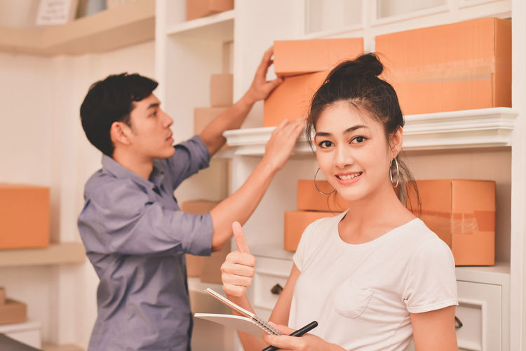 Adult Box - Container Casual Clothing Holding Indoors  Leisure Activity Lifestyles Men Occupation People Real People Side View Smiling Standing Technology Togetherness Two People Waist Up Women Young Adult Young Women