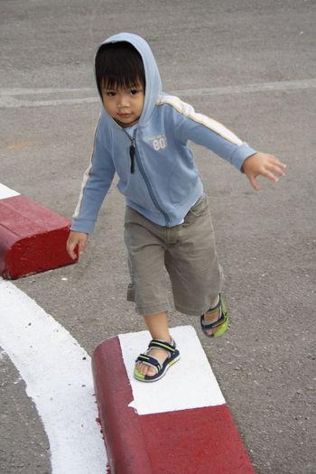 Portrait of cute boy walking on concrete block