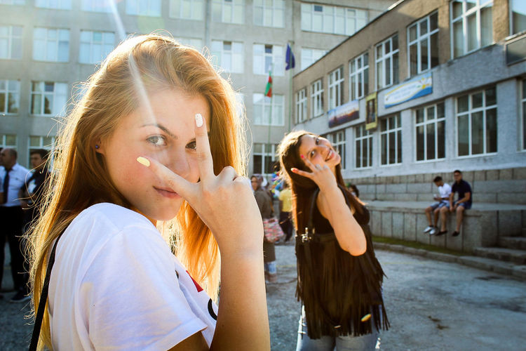 Portrait of smiling young friends showing peace sign on street