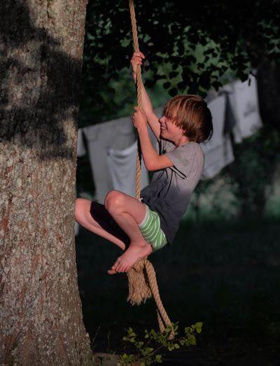 Full length of boy swinging on rope