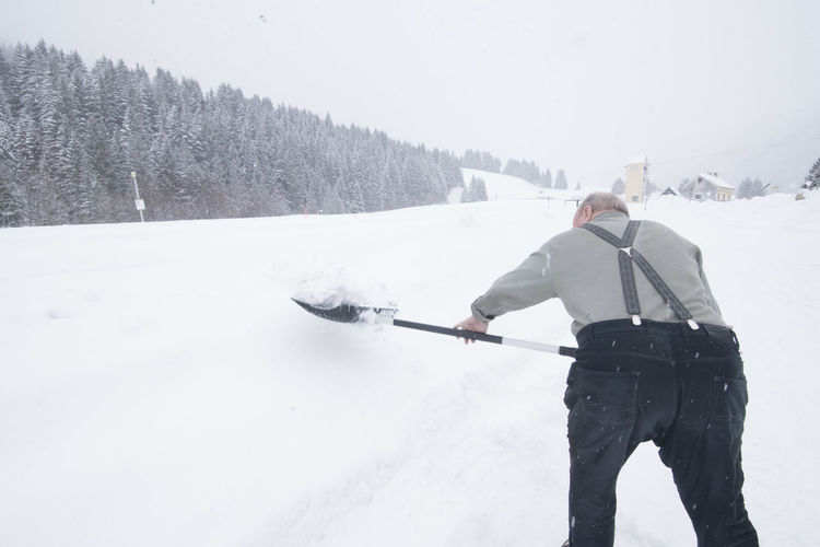 Rear view of man skiing on field during winter