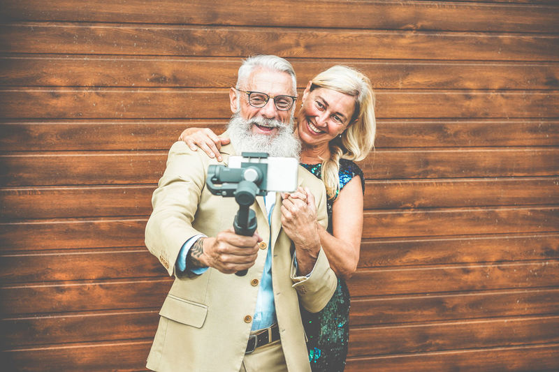 Smiling Senior Couple Taking Selfie Through Mobile Phone While Standing Against Wooden Wall