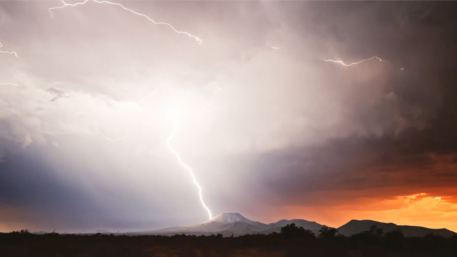 Panoramic view of lightning over mountain against sky during sunset