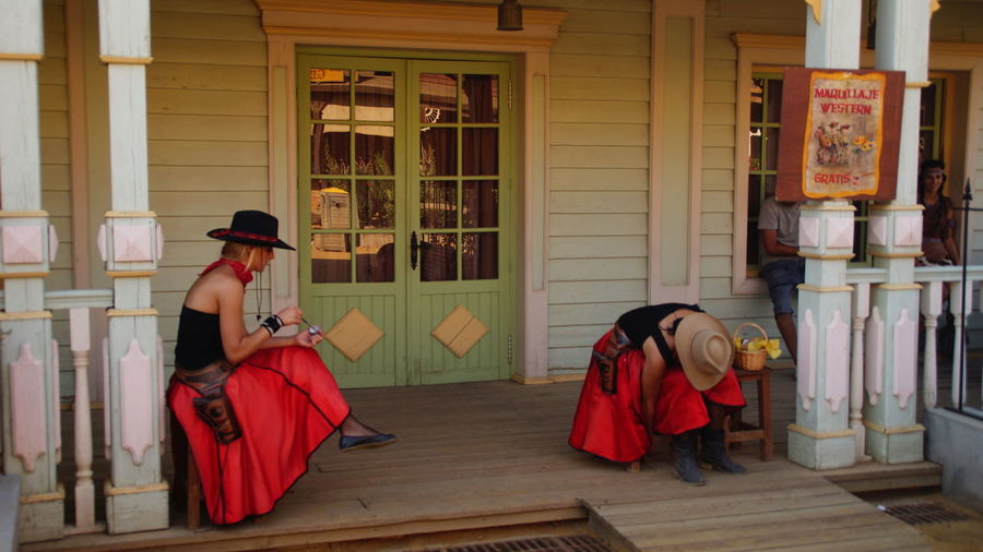 Women in traditional costume at porch