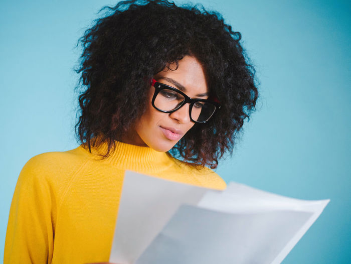 Young woman wearing eyeglasses reading documents against blue background