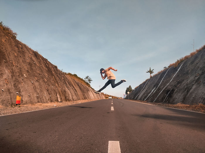 Man jumping on road against sky