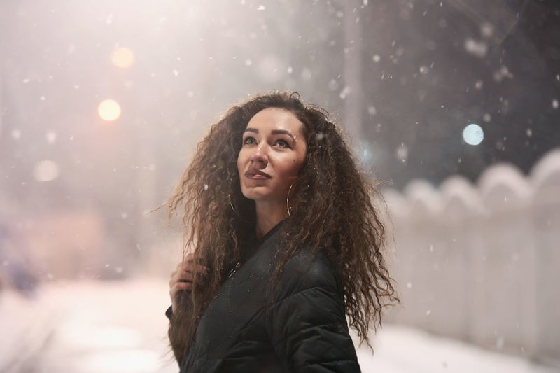 Portrait of young woman in snow during winter