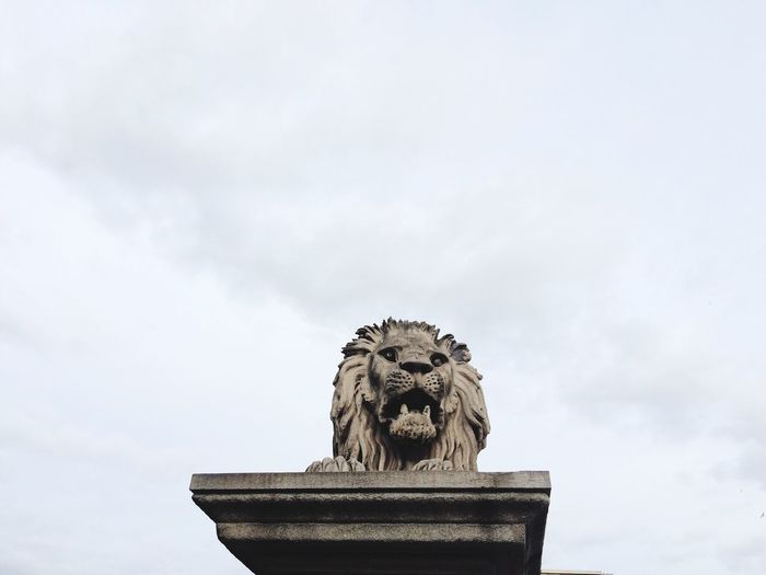 Low Angle View Of Lion Sculpture Against Cloudy Sky