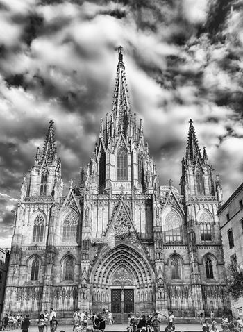 BARCELONA - AUGUST 10: Facade of the gothic Cathedral of the Holy Cross and Saint Eulalia, aka Barcelona Cathedral, Catalonia, Spain, on August 10, 2017 Built Structure Architecture Building Exterior Place Of Worship Building Religion Sky Spirituality Belief Travel Destinations Cloud - Sky Nature Travel Tourism Spire  City Gothic Style Outdoors Ornate