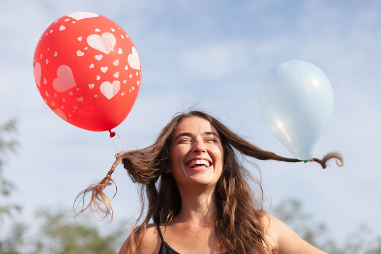young woman with balloons in her hair Funny Background Balloon Blue Sky Brunette Carefree Caucasian Cheerful Day Emotion Enjoyment Excitement Freedom Front View Fun Hair Happiness Nature One Person Outdoors Portrait Positive Emotion Smiling Women Young Adult