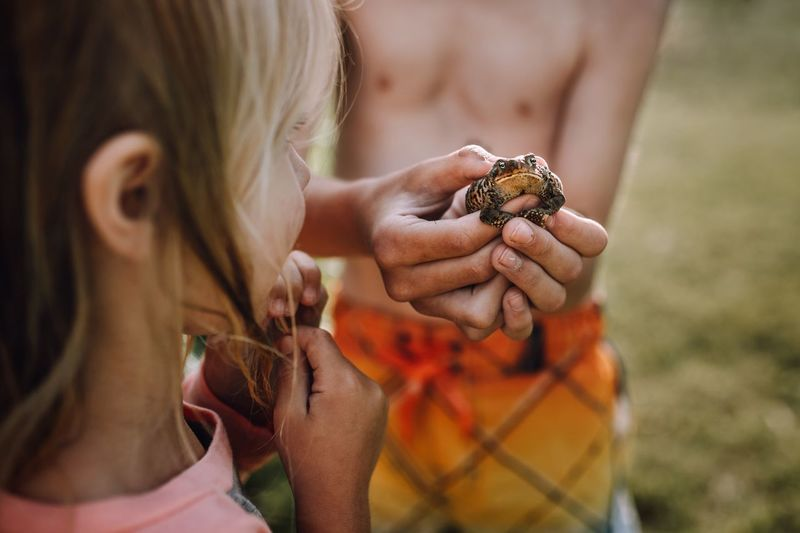 Girl by shirtless boy holding frog