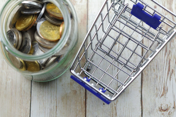 Mini cart beside a glass jar filled with coins Cart Trolley Wooden Background Money Money Money Money Coins Coins In A Jar Glass Jar Coins Trolley Expenditure Concept Conceptual Consumerism Background Copy Space Copyspace Jar High Angle View Directly Above Close-up Spending Money Shopping Basket Shopping Cart Groceries
