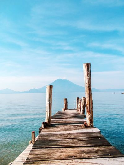 Tranquil scene. Volcano Landscape Volcano Lake Water Sky Sea Pier Architecture Built Structure The Way Forward Tranquil Scene Wood - Material Tranquility Nature Cloud - Sky Scenics - Nature Beauty In Nature Day Horizon Over Water No People Blue Outdoors