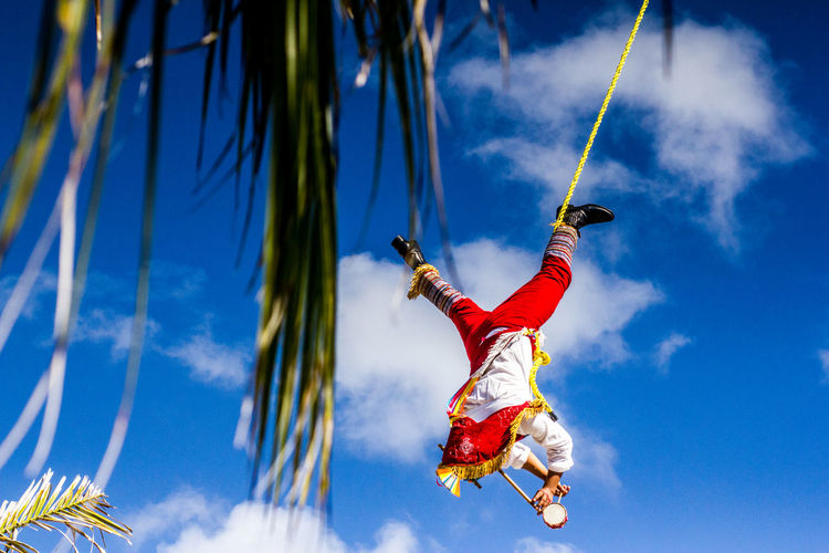 Low angle view of man hanging against blue sky