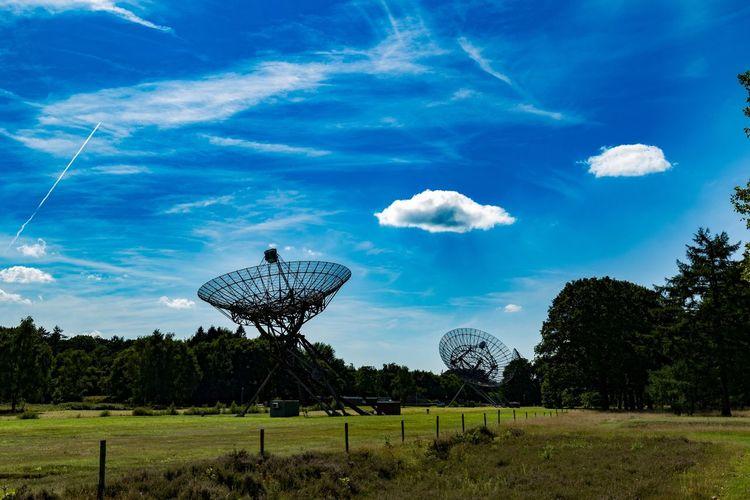 Silhouette radio telescopes against blue sky
