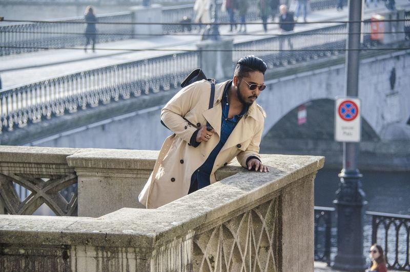 Young man looking down at bridge