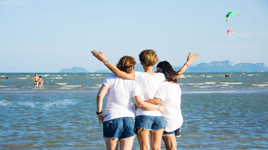 Rear View Of Friends Standing On Beach Against Sky