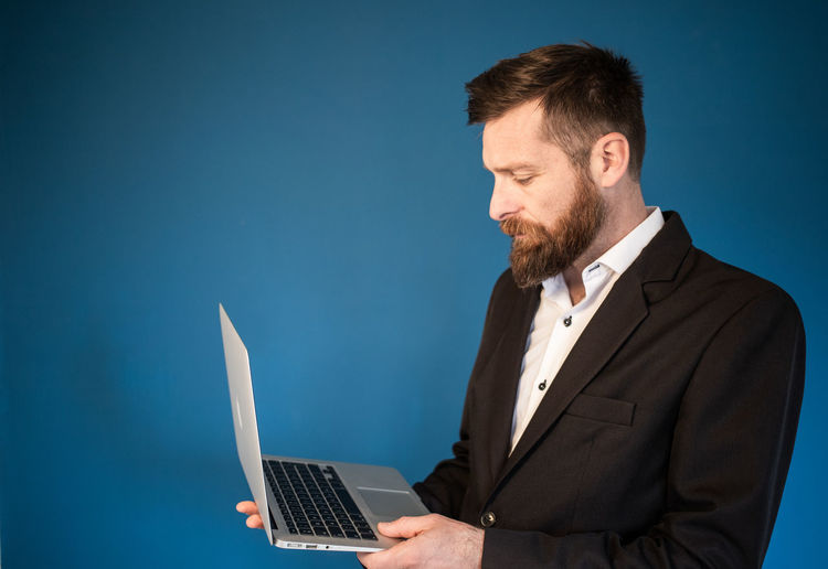 Man using smart phone against blue background