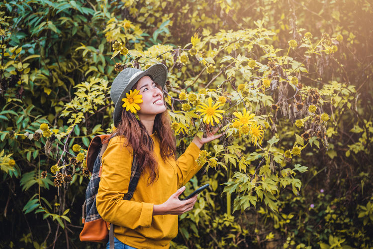 Full length of young woman standing against yellow plants