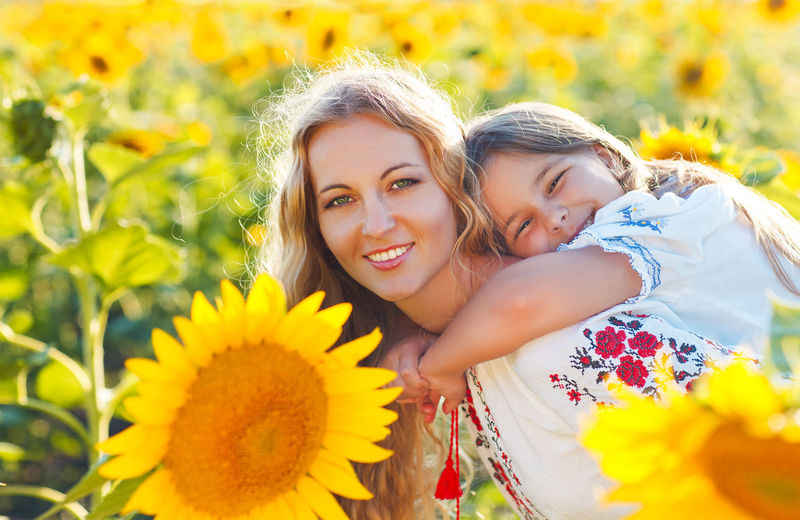 Portrait of smiling woman with yellow flower