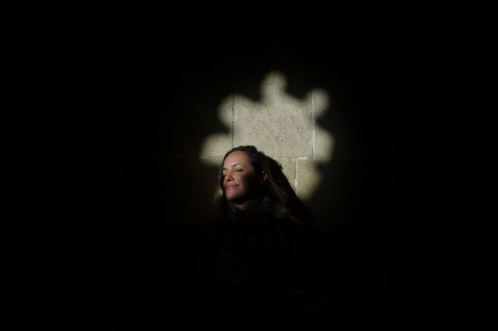 Woman sitting with sunshine on face Woman Adult Black Background Child Childhood Children Only Dark Escape Indoors  Night One Girl Only One Person People Shadow Sun On Face