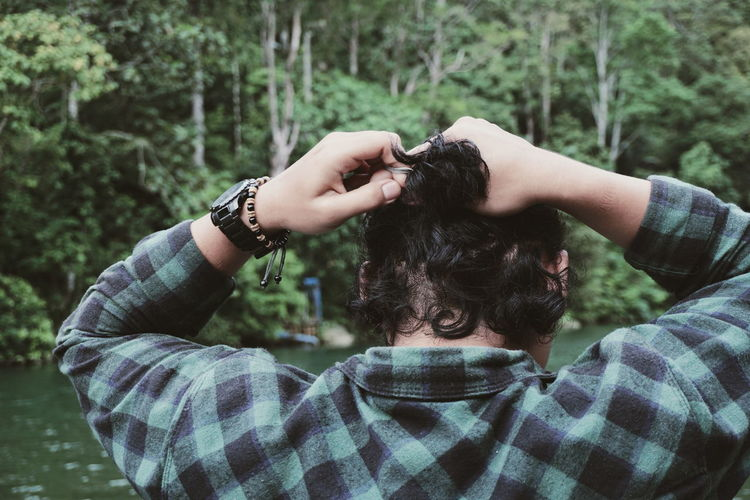 Rear view of man holding hair