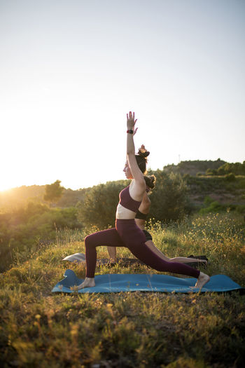 Women practicing yoga on mats against clear sky at sunset