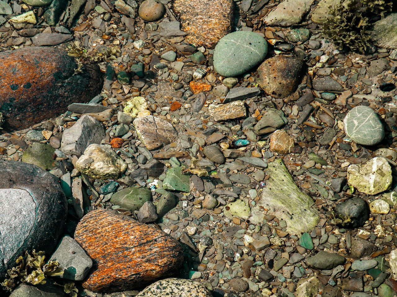 HIGH ANGLE VIEW OF STONES ON WET SHORE