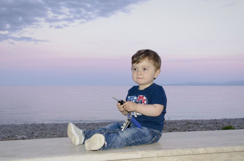 Cute toddler boy sitting with car key on retaining wall while looking away at beach against sky