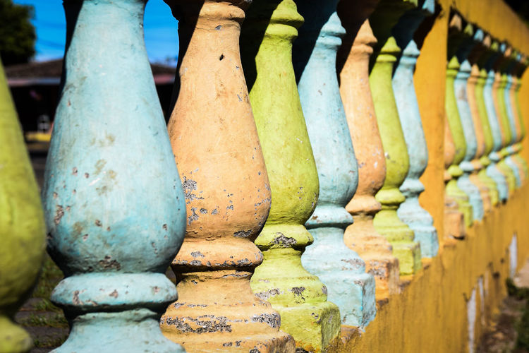 Close-up of row of multi coloured posts