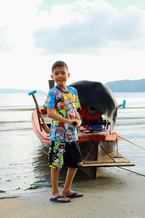 Beach Boy Boys Casual Clothing Childhood Day Elementary Age Front View Full Length Holding Leisure Activity Lifestyles Looking At Camera Nature Nautical Vessel Oar One Boy One Person Outdoors Portrait Real People Sea Sky Standing Water