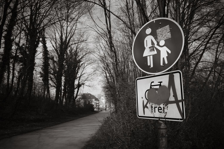 Road sign against trees