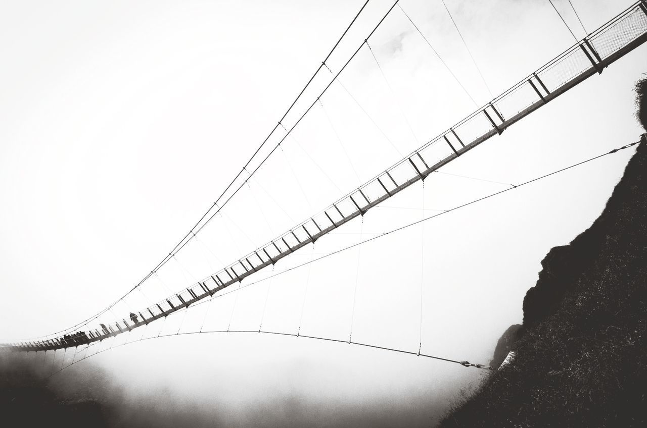 Low angle view of people walking on cable bridge in foggy weather
