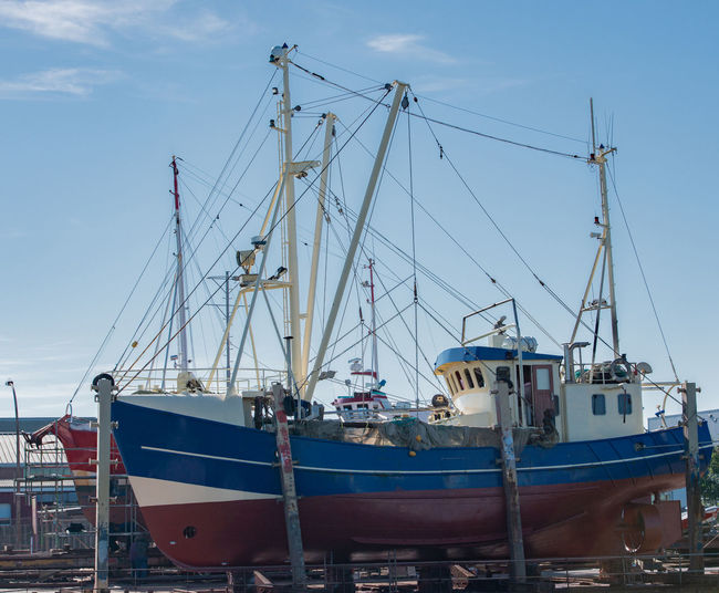 Fishing Boats Against Blue Sky At Harbor