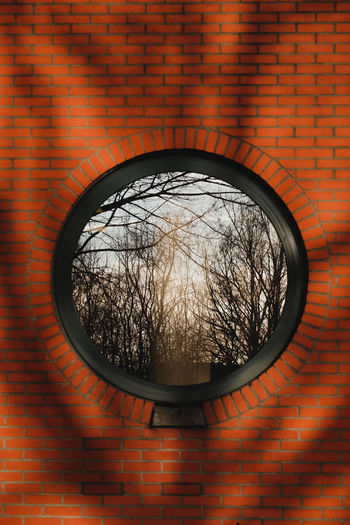 Trees reflecting in a round window in a red brick wall. Sun light comes through trees, that cast shadows on the wall Architecture Built Structure No People Brick Building Exterior Wall - Building Feature Tree Bare Tree Geometric Shape Wall Day Window Circle Low Angle View Outdoors Reflection Design Pattern Electric Lamp Light And Shadow TakeoverContrast Contrast And Lights Red Brick Round Window Holland