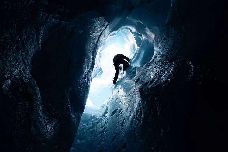 Silhouette person on ice in cave