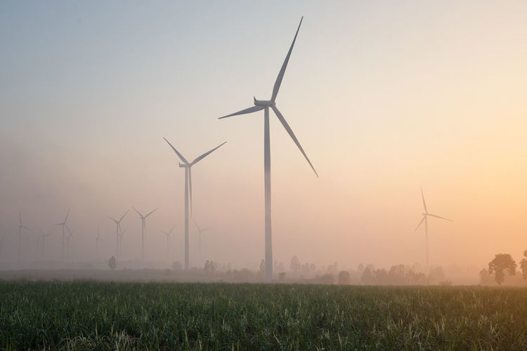 Wind turbines on field against sky during sunset