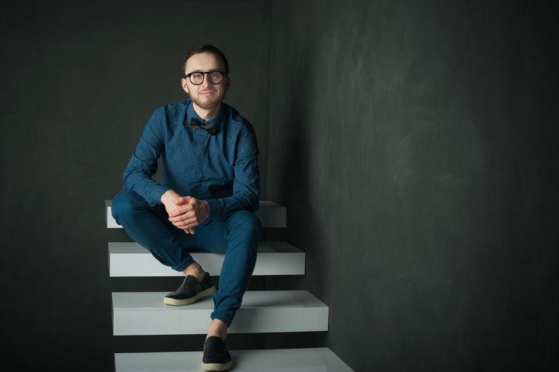 Portrait of man sitting on steps against black background