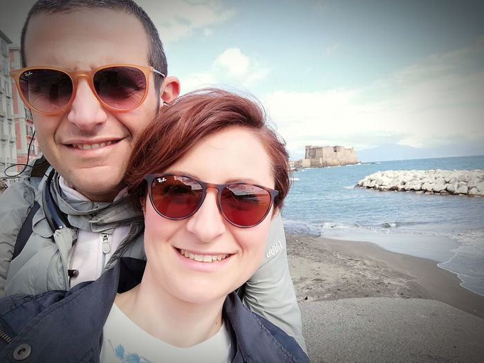 Smiling couple wearing sunglasses at beach