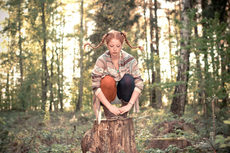 Full length of woman crouching on tree stump in forest