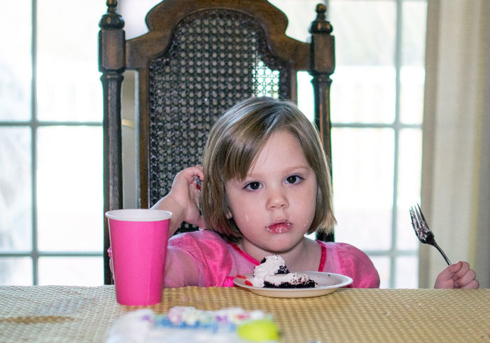 cute little girl seems to be in a daze as she sits with a piece of chocolate cake. sugar has not yet kicked in! Girls Portrait Childhood Table Child One Person Females Headshot Chair Looking At Camera Indoors  Front View Sitting Real People Seat Food And Drink Lifestyles Pink Color Innocence Birthday Cake Shy Celebration Treat Focus On Foreground Chocolate