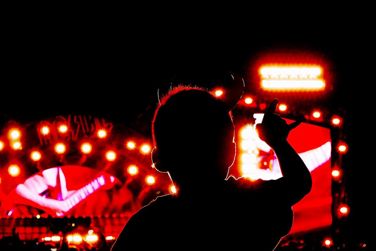 Silhouette boy at music concert against clear sky at night