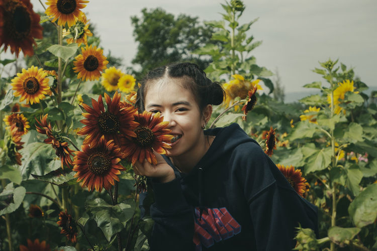 Portrait of young woman with sunflower on plant