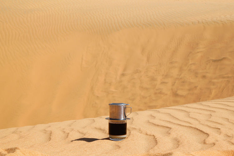 Drip Black Coffee in Vietnamese style with condensed milk on a red method of making in a desert. Breakfast Coffee Condensed Milk Copy Space Desert EyeEmNewHere Lifestyle Loneliness Morning Nature Sunlight Aroma Brewing Coffee Energy Hot Drink Making Coffee Minimalism Morning Rituals No People Sand Sand Dune Shadow Still Life Traditional Vietnamese Coffee