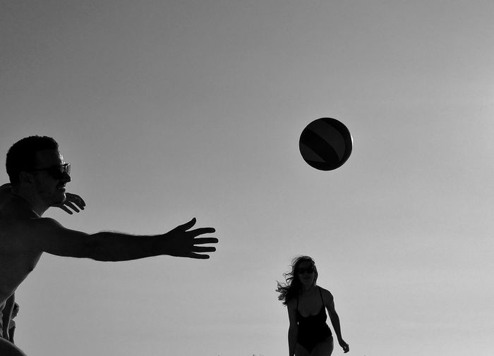 Woman Playing With Ball Against Clear Sky