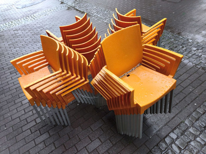 High angle view of orange chairs on table