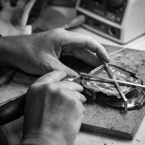 Cropped image of craftsperson working on metal at workshop