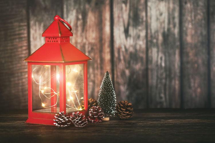 Illuminated lanterns on table against wall