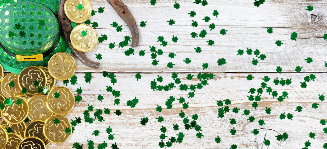 St Patrick day good luck hat, clovers and horseshoe with shiny gold coins forming left border on rustic white wooden boards Clover Copy Space Gold Green Color Hat Horseshoe St Patrick's Day Wood Irish St Patrick