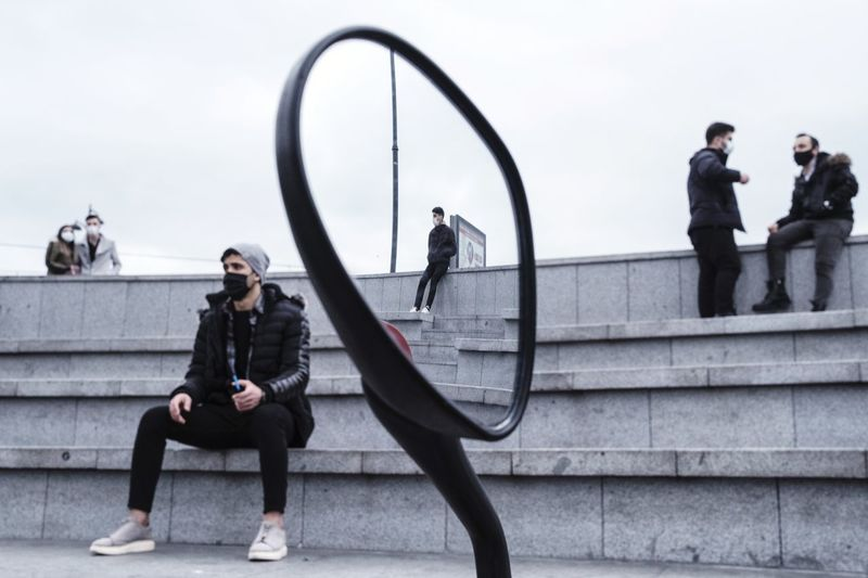 People sitting on staircase against sky